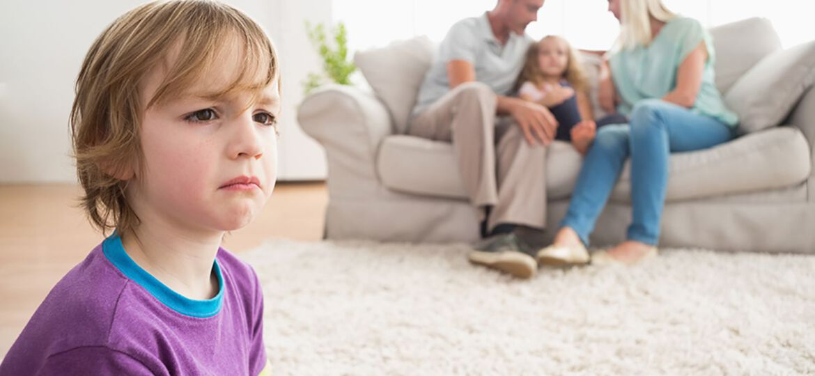 Upset boy sitting on floor while parents enjoying with sister on sofa at home